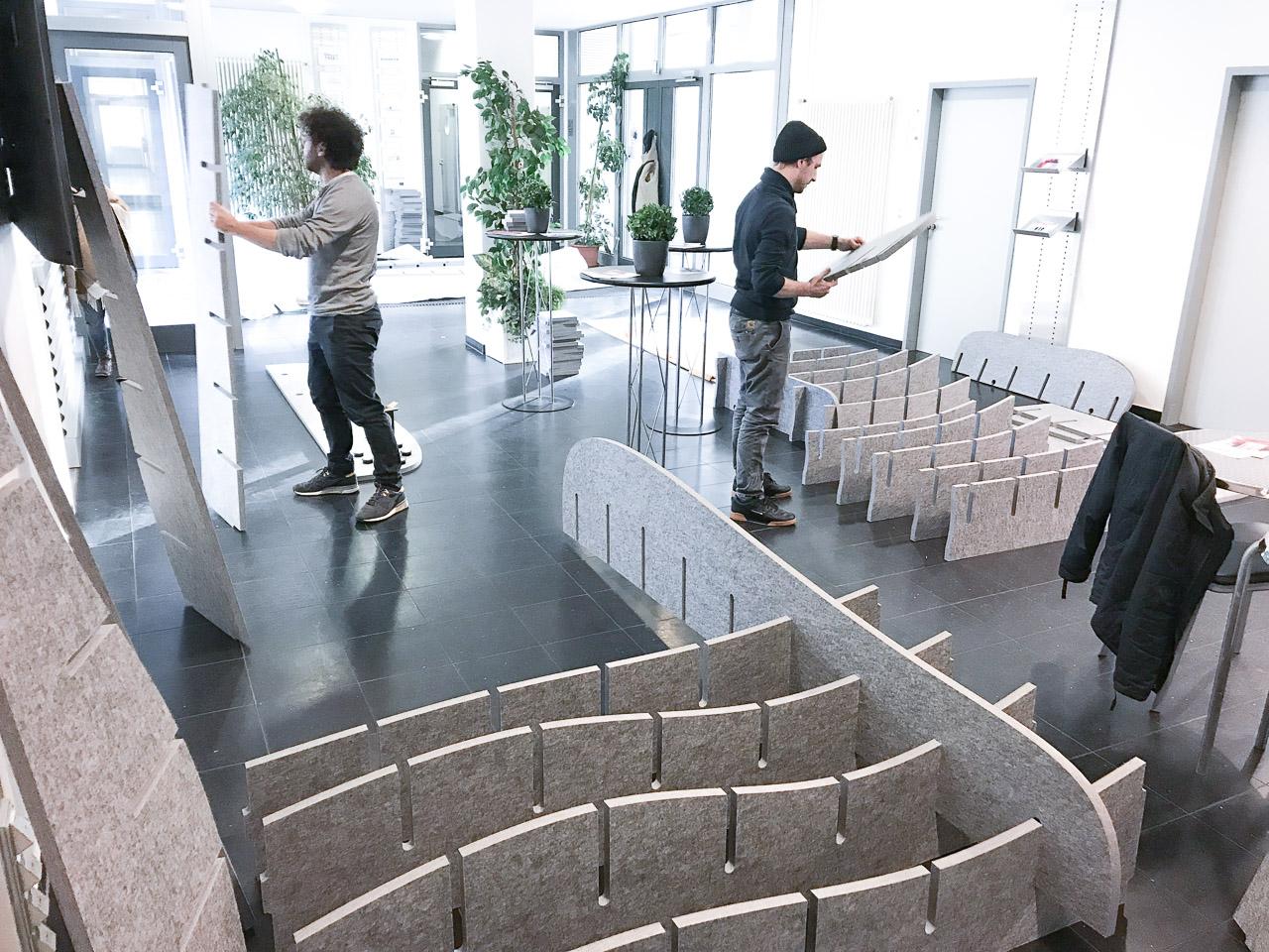 Zwei Personen bauen Akustikmöbel von AkustikKompetenz in einem Foyer oder Eingangsbereich auf.
