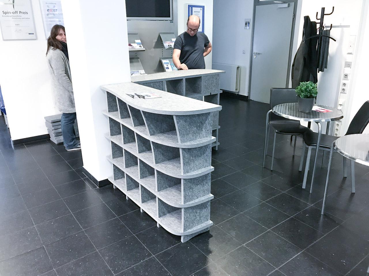 Zwei Mitarbeiter schauen sich das zusammengebaute Akustikmöbel von AkustikKompetenz an.